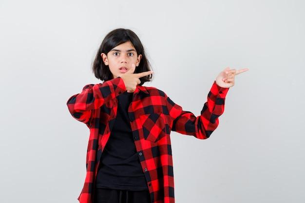 Tienermeisje wijst naar de rechterkant in t-shirt, geruit hemd en kijkt verbijsterd, vooraanzicht.