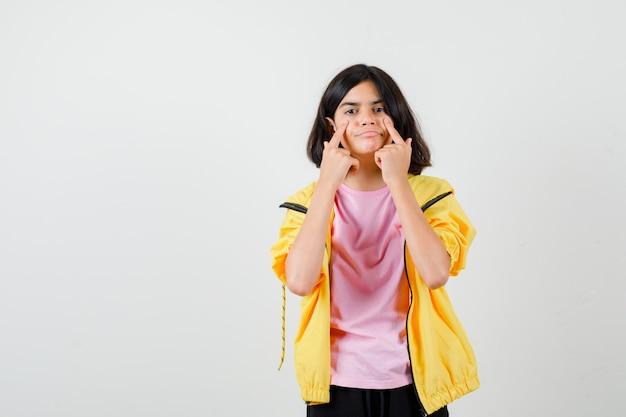 Tienermeisje wijst naar haar ogen in t-shirt, jas en kijkt gefocust, vooraanzicht.