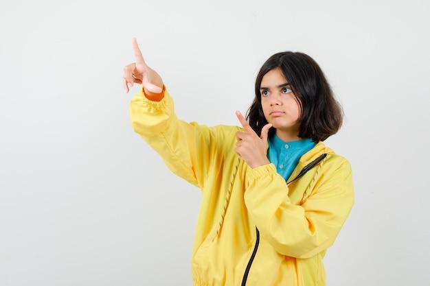Tienermeisje wijst weg in gele jas en kijkt gefocust, vooraanzicht.