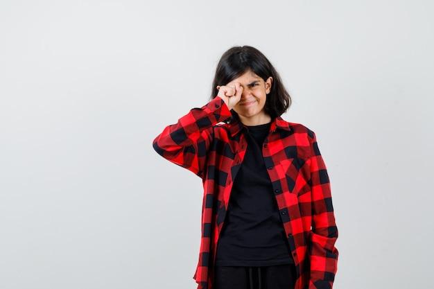 Tienermeisje wrijft over haar oog in een casual shirt en kijkt nieuwsgierig, vooraanzicht.