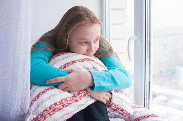Tienermeisje zit bij de vensterbank en kijkt uit raam