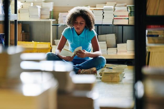 Tienermeisje zit onder stapels boeken in bibliotheek en leesroman