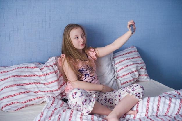 Tienermeisje zit op het bed en maakt selfie