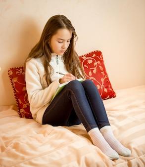 Tienermeisje zittend op bed en gedichten schrijven in notebook