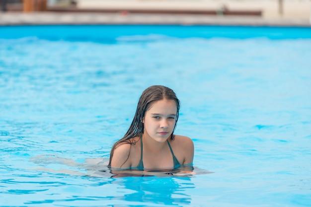 Tienermeisje zwemt in het heldere blauwe water van een zwembad tijdens een vakantie in een warm tropisch land