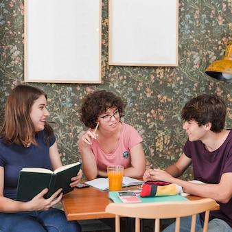 Tienermeisjes die aan vriend luisteren terwijl het bestuderen