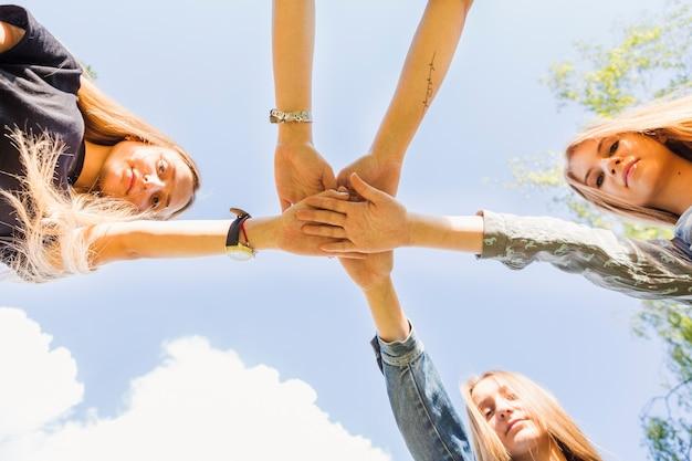 Tienermeisjes die handen samen houden