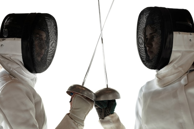 Tienermeisjes in kostuums schermen met zwaarden in handen geïsoleerd op wit