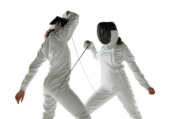 Tienermeisjes in kostuums schermen met zwaarden in handen geïsoleerd op witte studio achtergrond. jonge vrouwelijke modellen oefenen en trainen in beweging, actie. copyspace. sport, jeugd, gezonde levensstijl.
