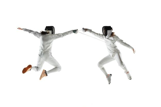 Tienermeisjes in kostuums schermen met zwaarden in handen geïsoleerd op witte studio achtergrond. jonge vrouwelijke modellen oefenen en trainen in beweging, actie. copyspace.