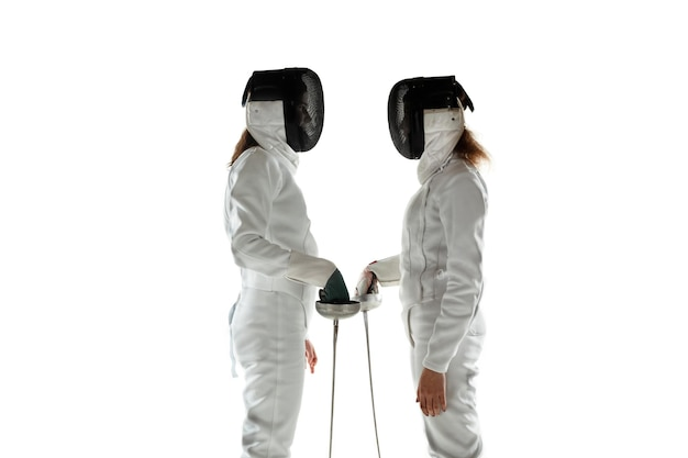 Tienermeisjes in kostuums schermen met zwaarden in handen geïsoleerd op witte studio achtergrond. jonge vrouwelijke modellen trainen, zelfverzekerd poseren. copyspace. beweging, actie.