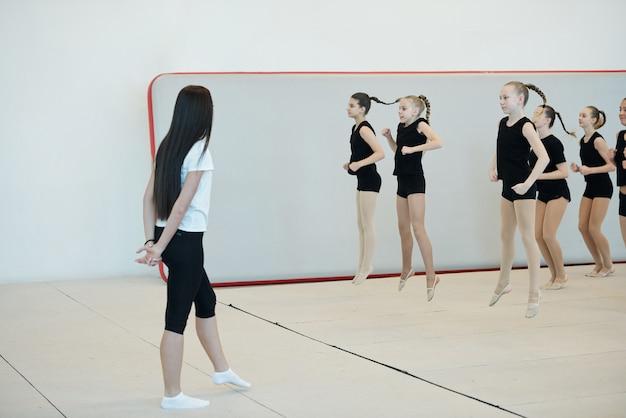Tienermeisjes in zwarte t-shirts en korte broeken springen op tijdens de warming-up onder controle van de instructeur bij cheerleading training