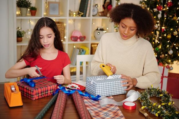 Tienermeisjes inpakken cadeautjes voor kerstviering thuis