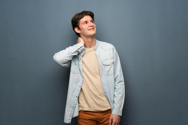 Tienermens die met het jasje van jean over grijze muur een idee denken terwijl het krassen van hoofd