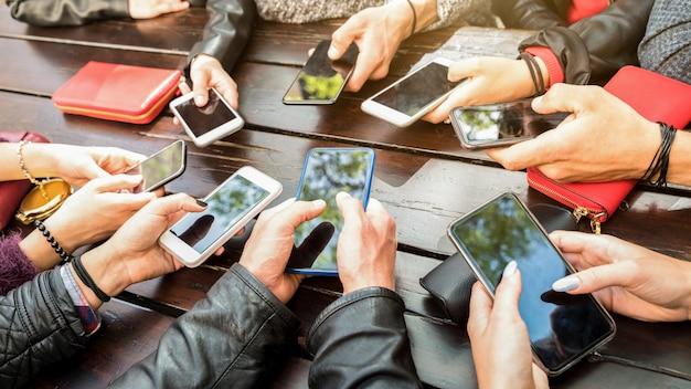 Tienermensen die pret hebben die mobiele slimme telefoons gebruiken