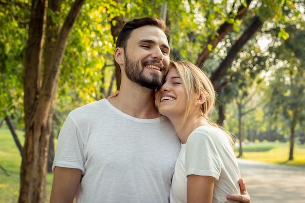 Tienerparen tonen liefde voor elkaar in het park. paren oefenen 's ochtends in het park. concept van jong koppel in het park.