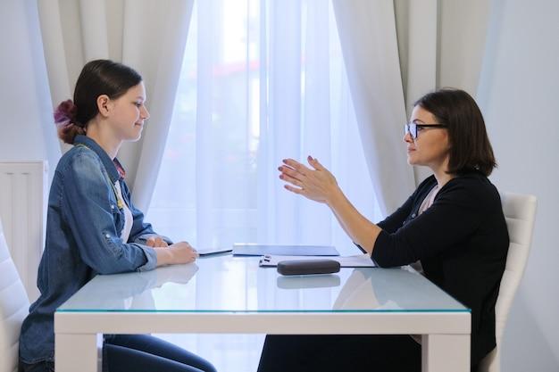 Tienerpsycholoog, vrouwelijke maatschappelijk werker die aan tiener spreekt