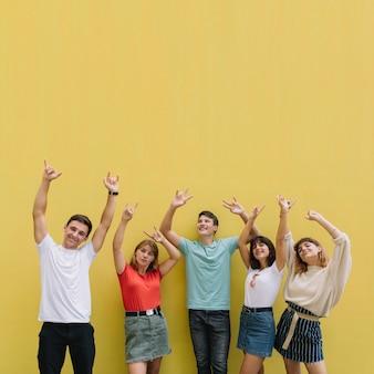Tieners bij het festival van de de zomermuziek die goede tijd op een gele achtergrond hebben.