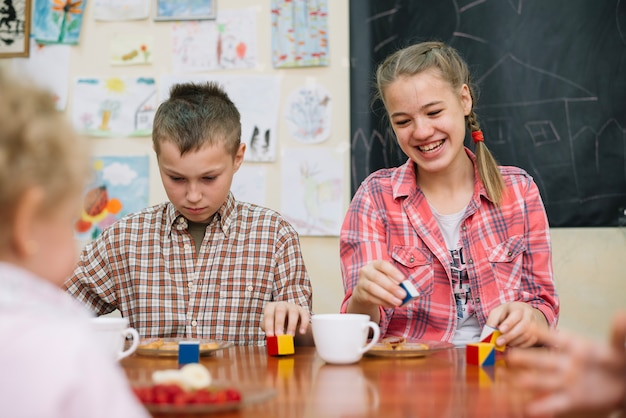 Tieners die aan tafel zitten spelen glimlachen