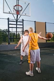 Tieners die basketbal spelen