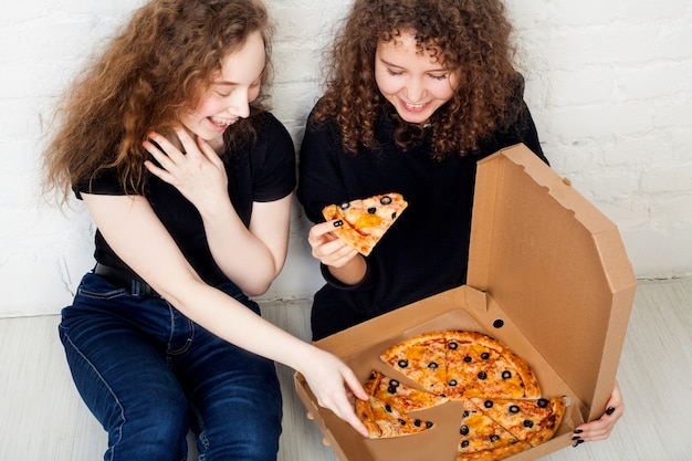 Tieners die een doos pizza houden en glimlachen. concept van pizzabezorger.