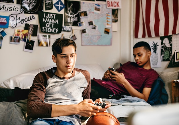 Tieners die in een slaapkamer hangen die een videospelletje spelen en een smartphone gebruiken