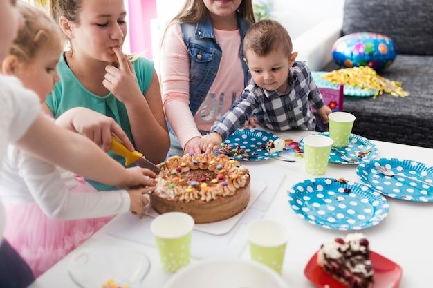 Tieners en kinderen proeven en snijden cake