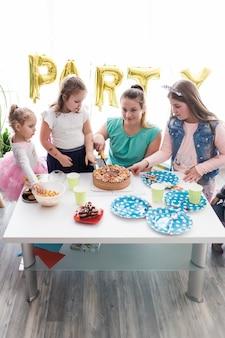 Tieners en kinderen snijden cake