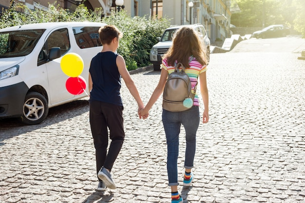Tieners hand in hand achteraanzicht. vriendschap, eerste liefde.