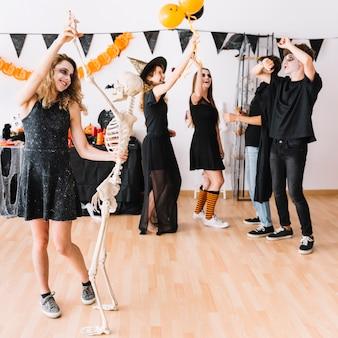 Tieners in donkere kleren glimlachend en dansen op feestje