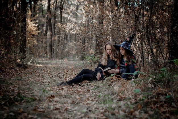 Tieners in halloween-kostuums in het bos. halloween-heksen lezen een boek in het bos.