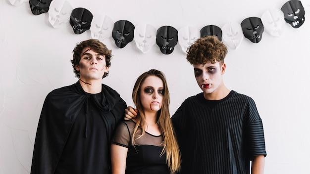 Tieners in halloween-kostuums van zombie en vampieren