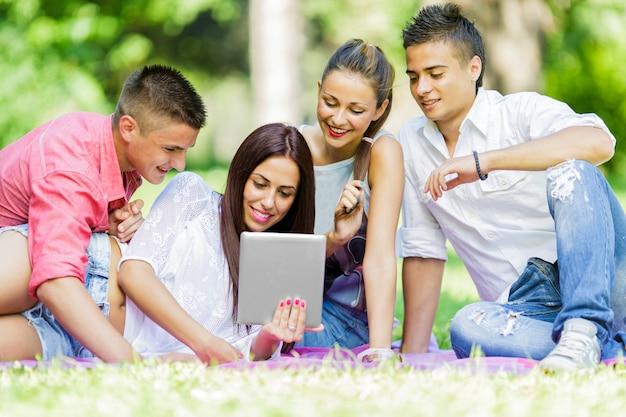 Tieners in het park met tablet