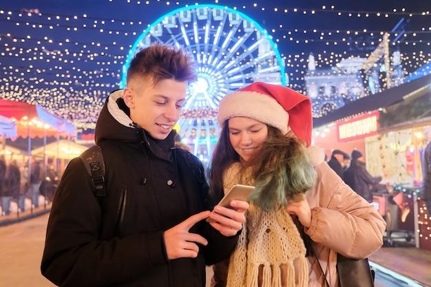 Tieners jongen en meisje op de kerstmarkt, in kerstmuts, met een smartphone