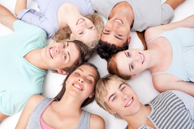 Tieners liggen samen op de vloer met hoofden