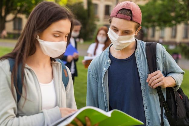 Tieners met gezichtsmaskers bespreken project