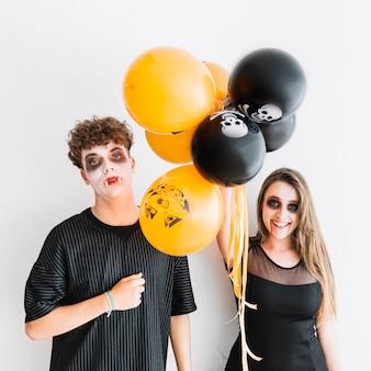 Tieners met grimmige halloween staan met oranje en zwarte lucht ballonnen