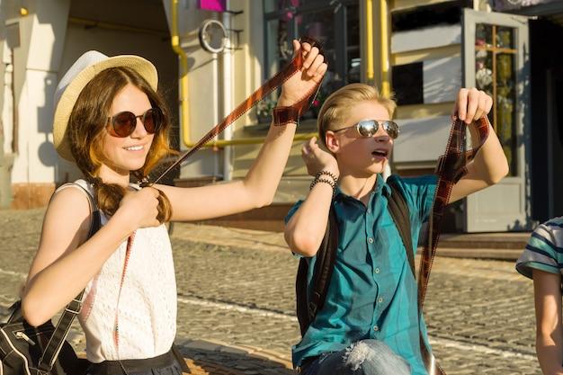 Tieners met interesse en verrassing kijken naar filmfoto-negatieven