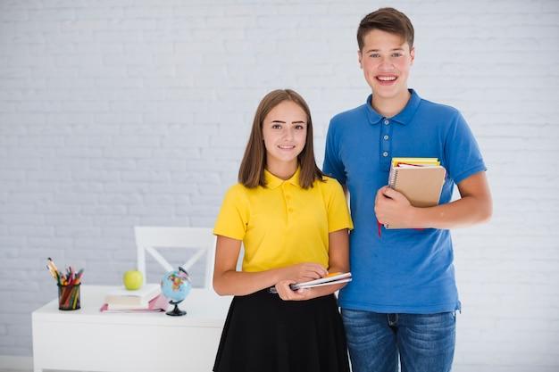Tieners met notitieboekjes in de klas