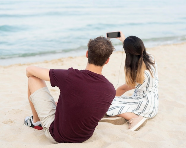 Tieners nemen een selfie samen op het strand