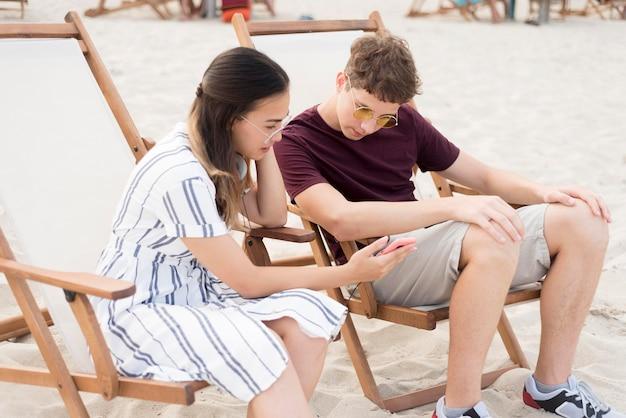 Tieners ontspannen samen op het strand