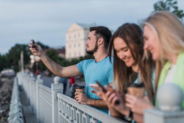Tieners rusten op een reling en nemen foto's