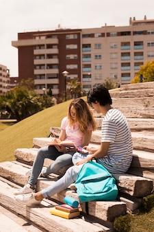 Tieners samen studeren op trappen in straat