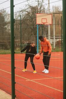 Tieners spelen basketbal buiten