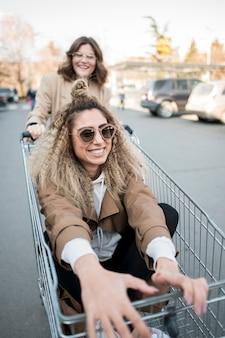 Tieners spelen met winkelwagen