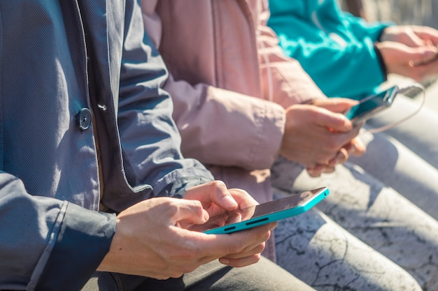 Tieners spelen spelletjes, schrijven tekst op telefoons. jonge mensen houden smartphones terwijl ze zitten o