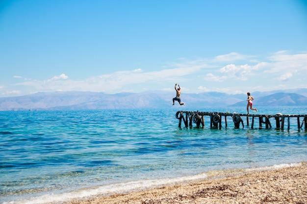 Tieners springen uit de pier in de zee.