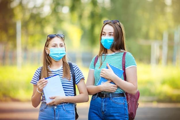 Tieners studenten meisjes met medische maskers tegen smog in de stad en voor bescherming tegen coronavirus gaan in de zomer de straat op met boeken naar lessen. terug naar school.