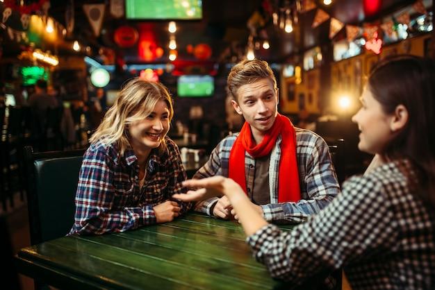 Tieners zitten aan de tafel in de sportbar