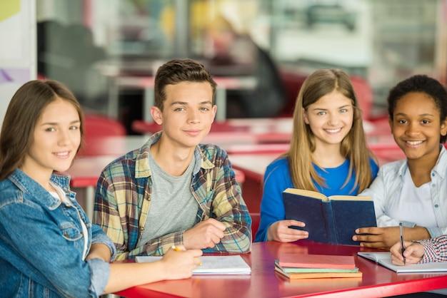 Tieners zitten aan de tafel
